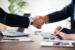 two men in suits at business meeting shaking hands
